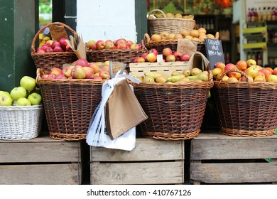 Apples and pears in a market stall, with vintage wooden boxes and baskets, and paper and plastic bags