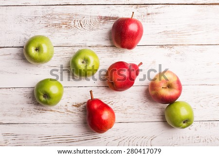 Apples and pears on the white wooden background