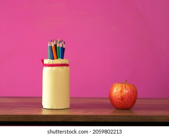 Apples and pencils on table at school wide shot selective focus