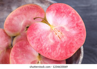 Apples with pink flesh on a dark gray background