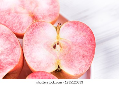 Apples with pink flesh on a white wooden background