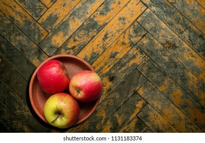 Apples in plate on wooden background