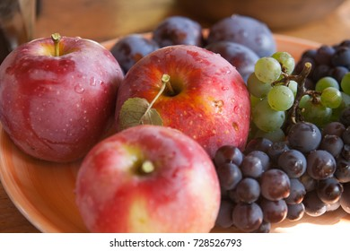 Apples, plums and grape on a wooden background, freshly washed on a plate
