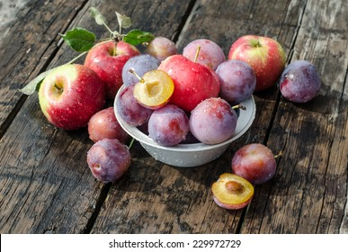 apples and plums on a wooden table