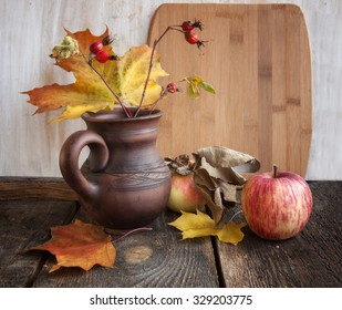 apples, rosehips maple leaves in a clay jug on a simple wooden table