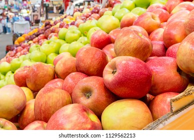 Apples for sale in a market. Red apples are closest, green apples farther away. shallow dept of field.