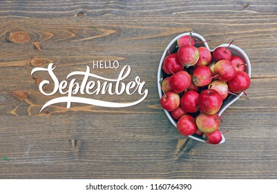 Apples in shape of heart on wooden background with hand lettering Hello September. Autumn harvest of fresh apples top view.