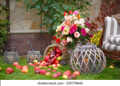 apples spilled from the basket on the green grass. Autumn flowers