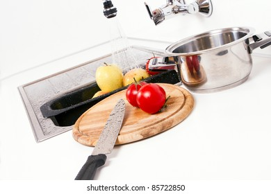 Apples and tomatoes prepared in the kitchen.