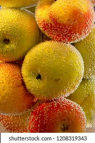 Apples in a vase of soda water, bubbles and water all around the yellow and red apples