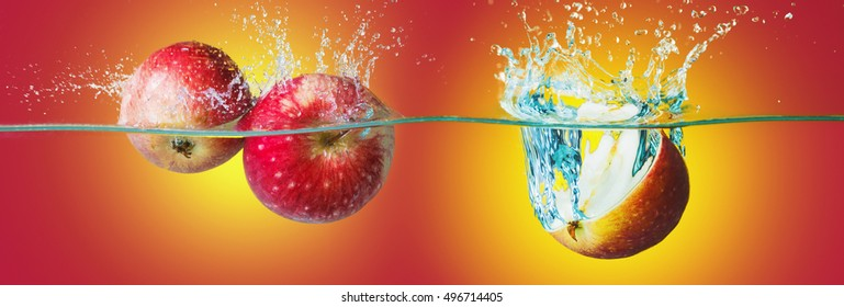 Apples with water splash over bright yellow-red background