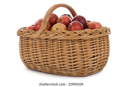 Apples in wicker basket on white background.