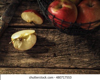 Apples in wire basket on an old wooden background