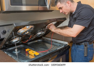 Appliance technician troubleshooting an electric stove top burner, inside of a home.