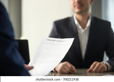 Applicant holding employment agreement, considering work terms, reading position duties before signing official labor contract, successful vacancy candidate getting hired, job placement, close up