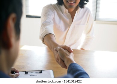 The applicant smiled glad that the manager accepted the job. Success in a job interview. The trick is to write a resume, qualifications, applicants, skills to answer questions and prepare.