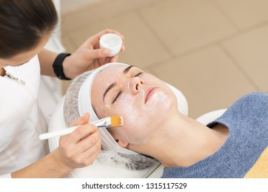 Application of anesthetic cream process to woman before aesthetic laser polishing procedure or injections in the cosmetology medical clinic, beauty salon.