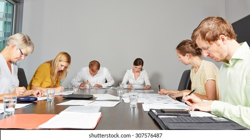 Application candidates in assessment center filling out test forms