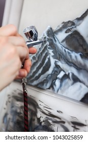 The application of color with airbrush spraying with compressed air, close-up view
