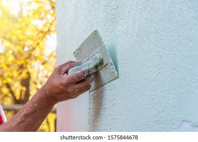 Application Of Facade Plaster,Worker Plastering The Facade Of The Building, Close-Up.