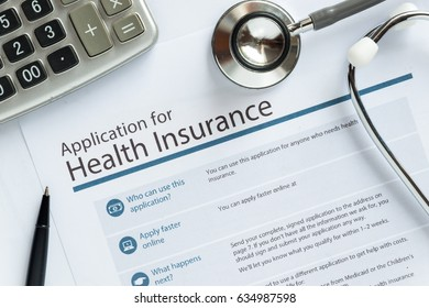 Application for health insurance paper form is overlapped by calculator and stethoscope concept for life planing.