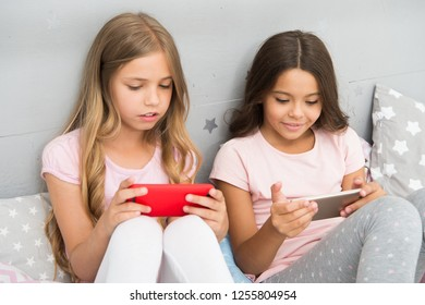 Application for kids fun. Internet surfing and absence parental advisory. Smartphone internet access. Girls sisters wear pajama busy with smartphones. Children in pajama interact with smartphones.