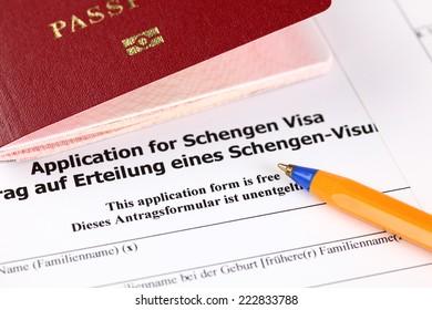 Application for Schengen visa, passport and pen.