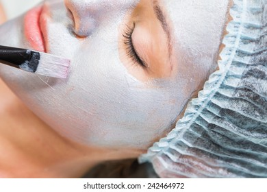 Application of the silver mask on the face of the girl. Cosmetic procedures for the face. Beautician facial treatment at a spa salon. The procedure to rejuvenate and nourish the skin of the face.