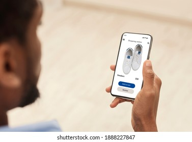 Application Or Website For Online Store. Over the shoulder view of black man using smartphone, browsing internet shop with shoes, choosing new sneakers footwear. Ecommerce, Retail, Sale And Discount