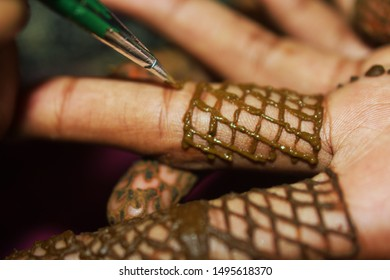 Applies a mehndi design in finder using henna. Mehndi tradition art of Indian bride