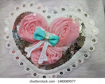 Applique for clothes in the form of a heart, inside a rose made of ribbon. Decorates lace and sequins on the outside. Delicate application colors complement the overall look.