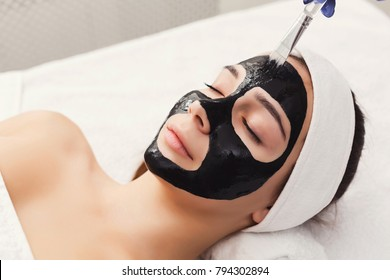 Apply black face mask, spa beauty treatment and skincare. Woman getting facial cleansing mask by beautician at spa salon, closeup