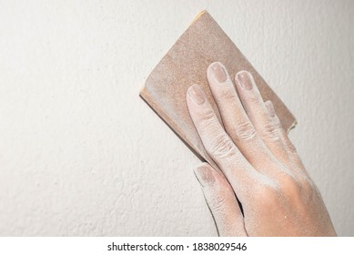 Apply pressure to sheet of sandpaper with hand to scraping wall , prepare smooth surface for paint wall