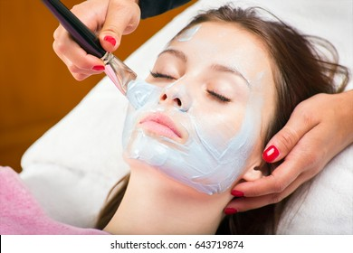 Applying blue cosmetology mask to young pretty woman face with wide brush