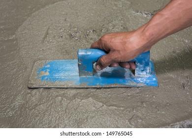 Applying construction trowel in wet cement