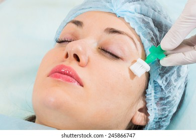 Applying cosmetic cream treatment on  face in spa salon. Beautiful young woman during facial treatment in cosmetic salon close up.