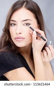applying cosmetic pencil on woman's eye