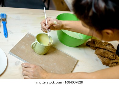 applying glaze to a ceramic Cup with a brush