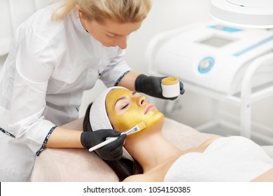 Applying of gold facial mask in beauty salon. Cosmetologist using brush for procedures. Anti wrinkle treatment prevent fine lines, making skin texture even, skin tone smooth and radiant.