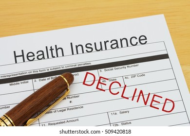 Applying for a Health Insurance Declined, Health Insurance application form with a pen on a desk with an declined stamp