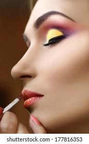 applying lipstick by makeup artist, backstage
