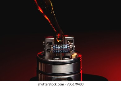 Applying liquid with nicotine in the coils on the RDA over the dark background
