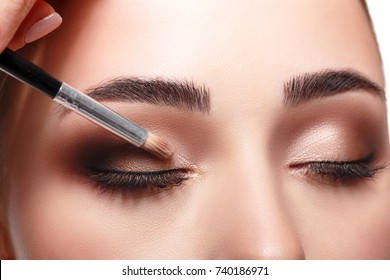 Applying makeup for beauty model, isolated on white background