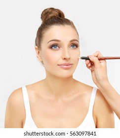 Applying Make-up. Woman with a brush for make-up