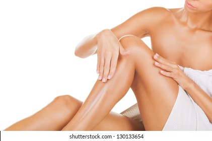 Applying moisturizer cream. Care for female legs isolated on white background
