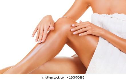 Applying moisturizer cream. Care for female legs isolated on white background