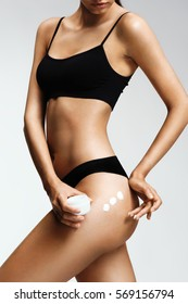 Applying moisturizer cream. Sporty girl in black lingerie cares about her buttocks. Beauty part of female body. Woman's shape with clean skin. Skin care concept