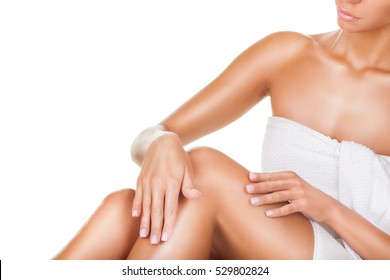 Applying moisturizer cream. Young woman caring for her legs on a white background