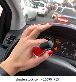 Applying nail polish in a car in crowded street