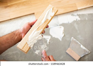 Applying of parquet glue on a floor plate using hand tools